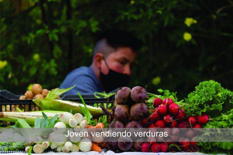 Joven vendiendo verduras